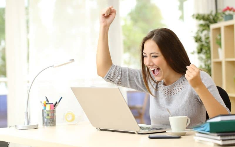 Co-working remotely got me a higher paying job within 4 months. Woman celebrating looking at laptop.